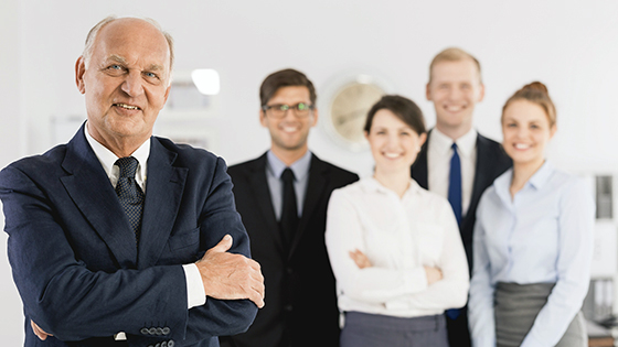 Elder businessman with his young employees